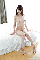 Seated nude on edge of bed small breasts wearing high heels