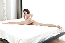 Naked on bed with legs stretched out fingering her pussy