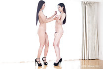 Standing naked face to face hands clasped long hair wearing high heels