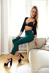 Sitting On Sofa Arm Wearing Black Bra In High Heels