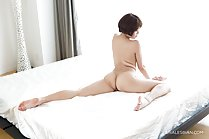 Seated on bed naked short hair bare feet